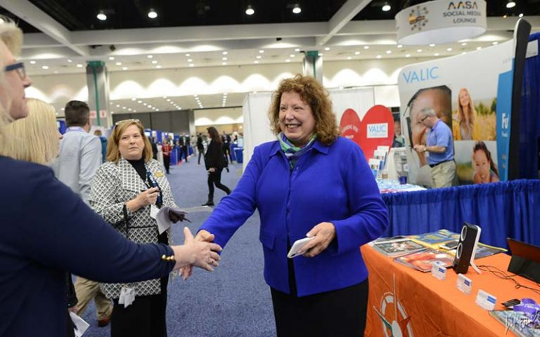 Education professionals shake hands at National Conference on Education booth